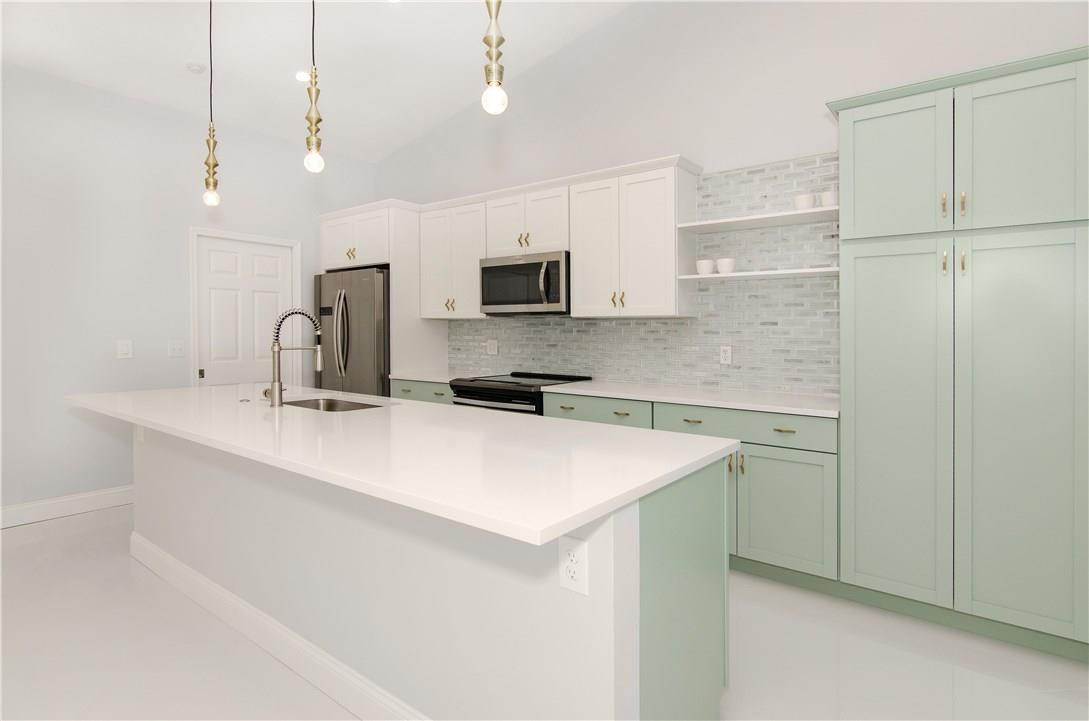 Mint green and white contemporary kitchen design with brass accents
