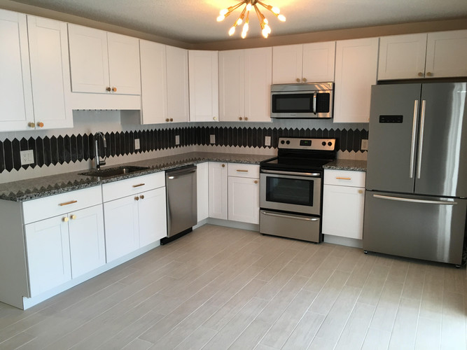 Modern kitchen with black and white backsplash and brass accents