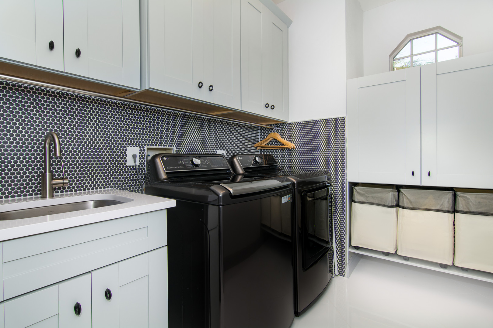 Gray laundry room cabinets with black matte penny tile