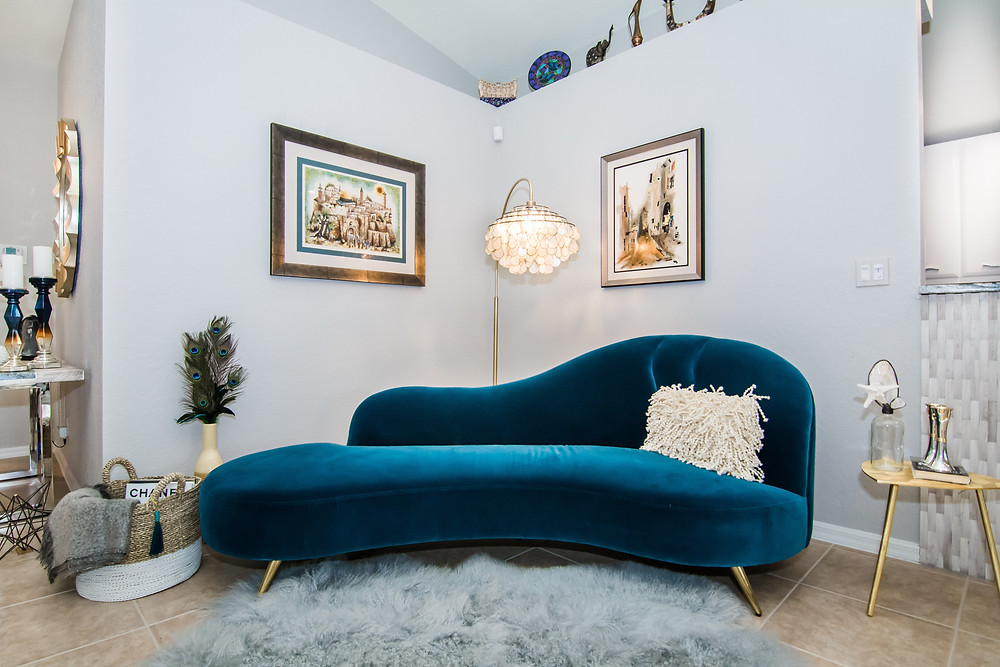 Teal peacock sofa from cb2.com, tibetan sheepskin rug, peacock feather decor, capiz lamp, and homegoods accessories