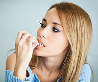 Woman biting her finger nails