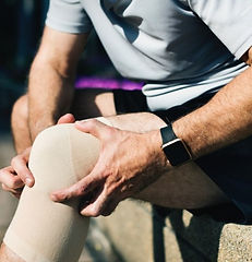 Man holding his painful damaged knee