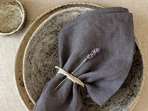 Gray linen napkin on modern ceramic plate