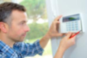 Electrician fitting an intrusion alarm.j