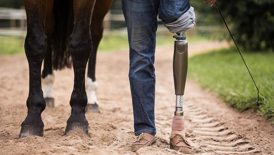 Pferdebeine daneben die Beine einer Person. Ein Hosenbein ist hochgekrempelt, man sieht eine Beinprothese.