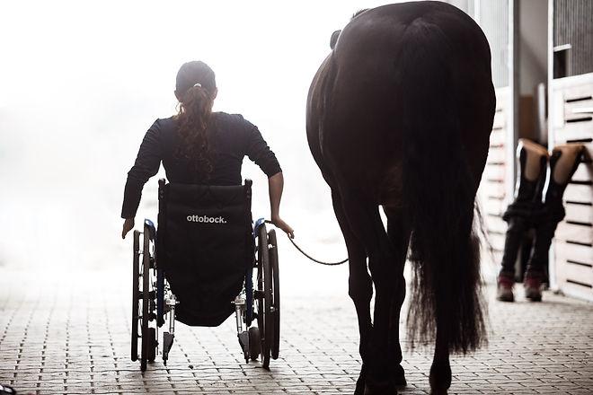 Julia Porzelt sitzt im Rollstuhl und führt ihr Pony Dainty aus dem Stall heraus. An der Seite lehnen zwei Beinprothesen an einer Boxenwand.