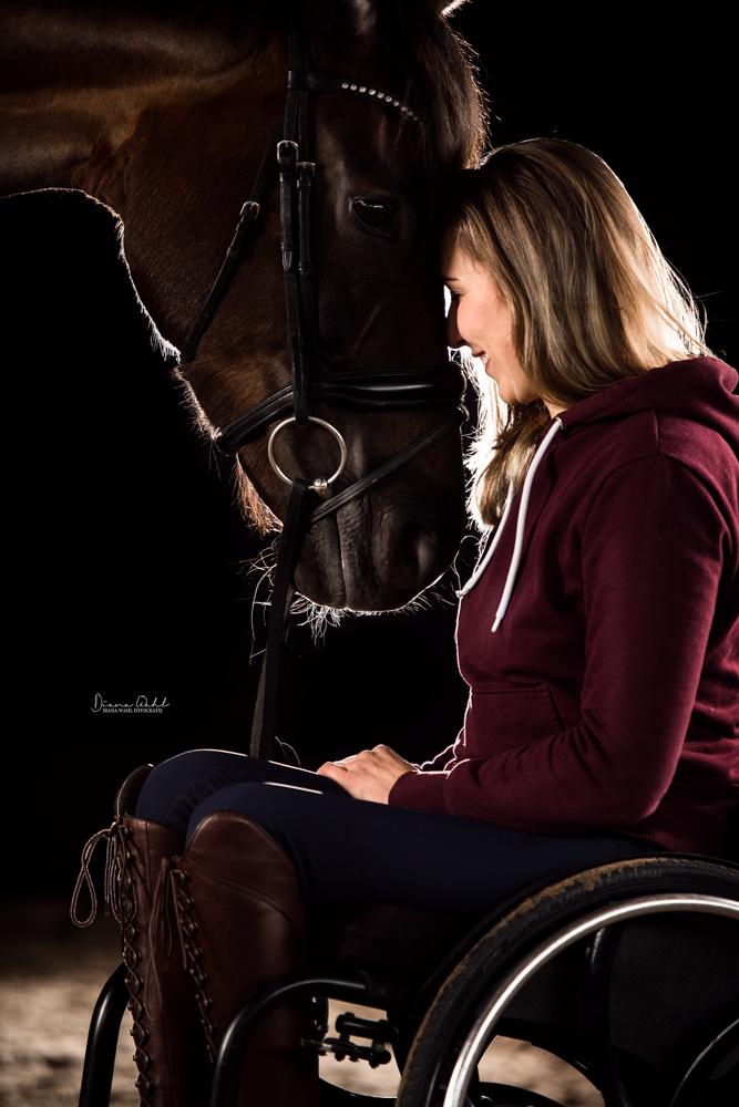 Gianna Regenbrecht mit ihrer Stute Selma. Gianna sitzt im Rollstuhl und Selma hat ihren Kopf gesenkt, so dass beide Stirn an Stirn die Köpfe zusammenstecken.