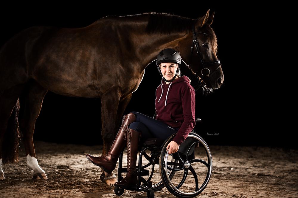 Gianna Regenbrecht zusammen mit ihrem Pferd Selma. Gianna sitz im Rollstuhl, die Beine überschlagen. Sie trägt Reithose, Reitstiefel und Reithelm.