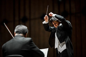 Dawid Runtz, conductor, photographed during a concert in an expressive pose, conducting with a baton at a concert hall