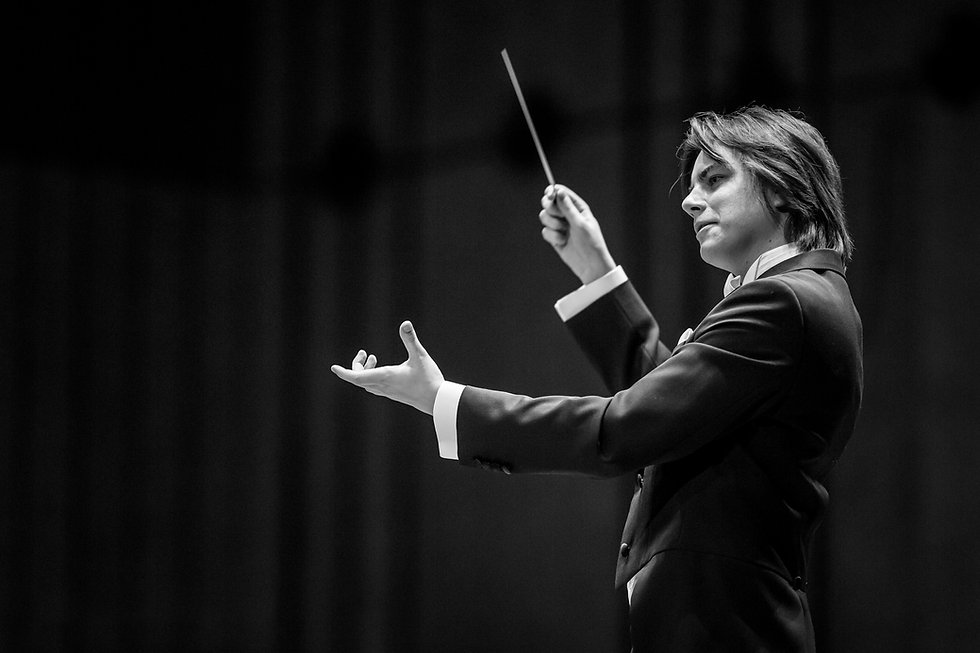 Dawid Runtz, conductor, photographed during a aconcert, conducts holiding a baton in a concert hall