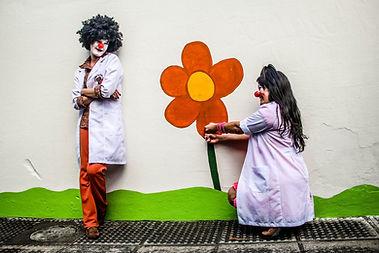 Dra. Chuchu e Dra. Pano de Chão segurando uma rosa pitada na parede