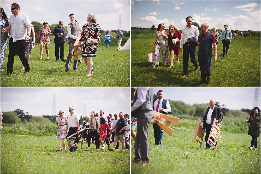 Wedding guests carrying benches across the grass at Cuttlebrook Farm