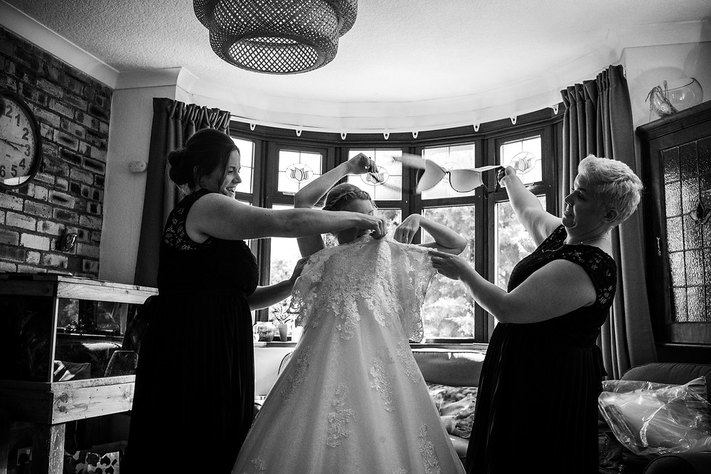 Bridesmaids helping bride take her bride off whilst she puts on her wedding dress