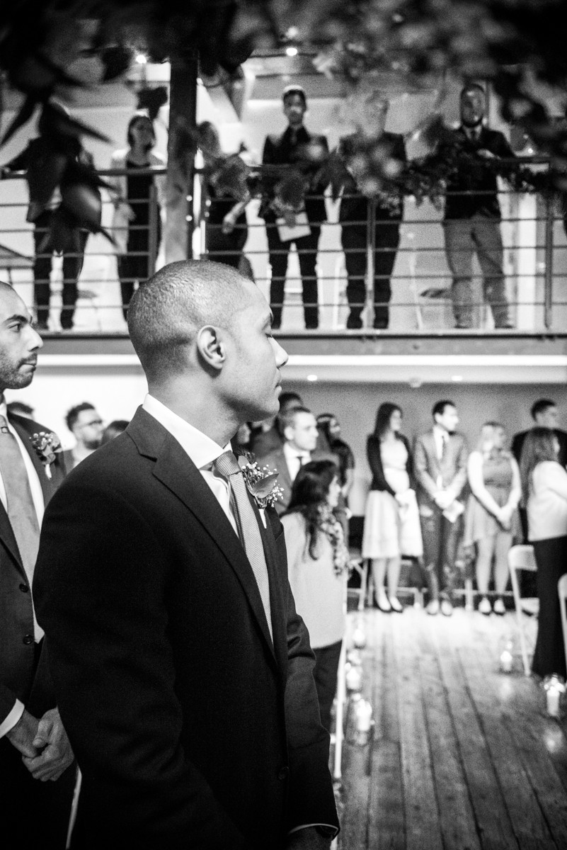 black & white reportage image of groom with his eyes closed waiting for bride at bristol wedding