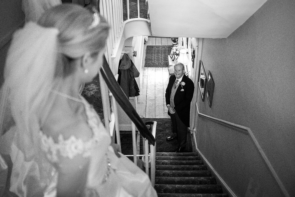 Father of the Bride looking up the stairs as he sees his daughter for the first time on her wedding day