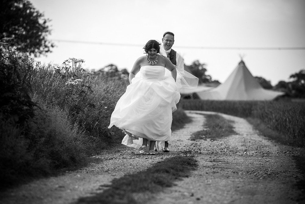 Groom holding the brides dress of the ground as they walk along a track at their Derbyshire tipi wedding