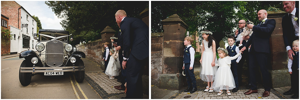 Bridal party waiting for wedding car to arrive outside St Mark's church in Brewood