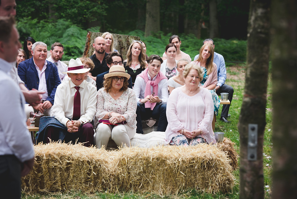 wedding guests sitting on hay bales during warwickshire wedding
