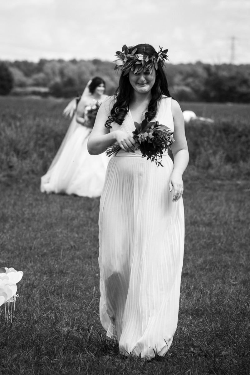 Crying bridesmaid walking across the grass at open air wedding next to the river Trent