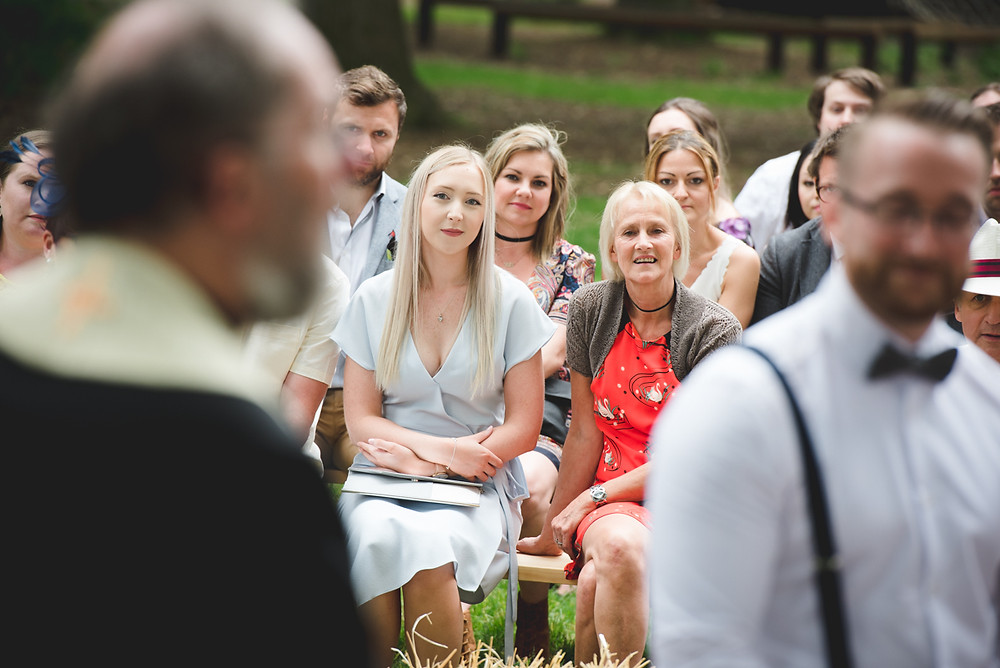wedding guests looking at vicar during outdoor ceremony