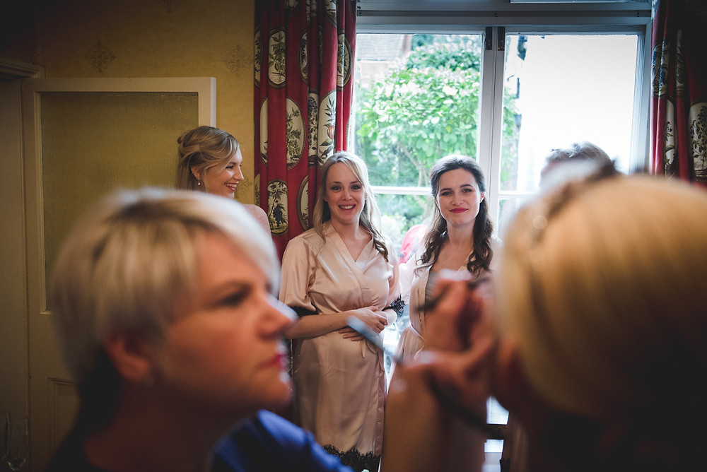 Bridesmaids looking on at Bride having her makeup done before Worcester wedding