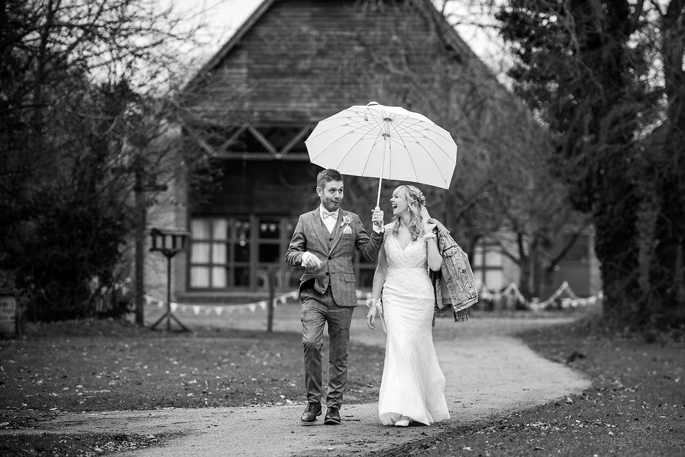 Black & white image of Bride & Groom walking away from New Guesten Hall at Avoncroft Museum Wedding
