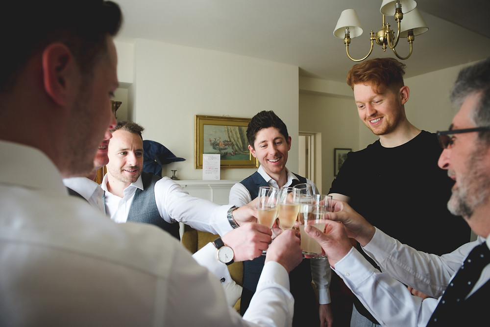 Groomsmen drinking champagne before Warwickshire wedding at Wethele Manor