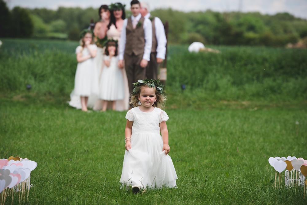 Flower girl walking across grass before outdoor Derbyshire wedding