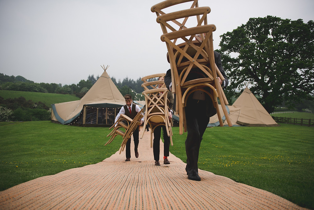 Guests carrying chairs from the tipi at Ludlow wedding