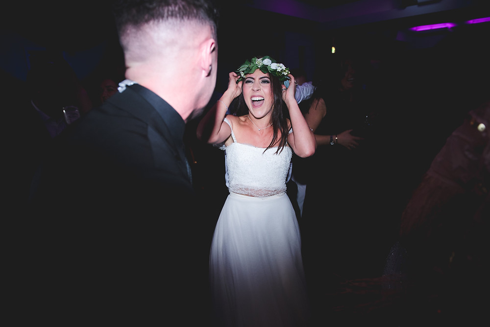 bride holding on to her flower crown during first dance at birmingham penthouse