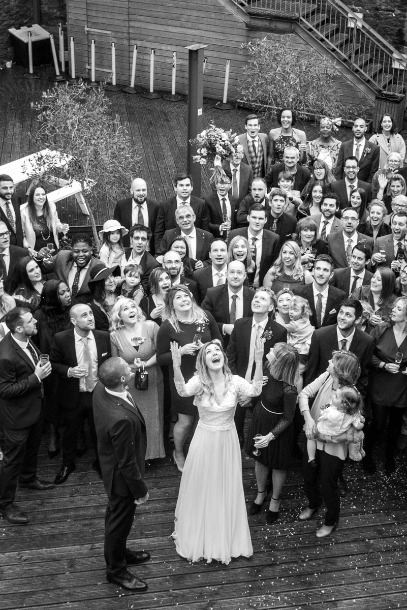 black & white photograph of guests waiting to catch bridal bouquet