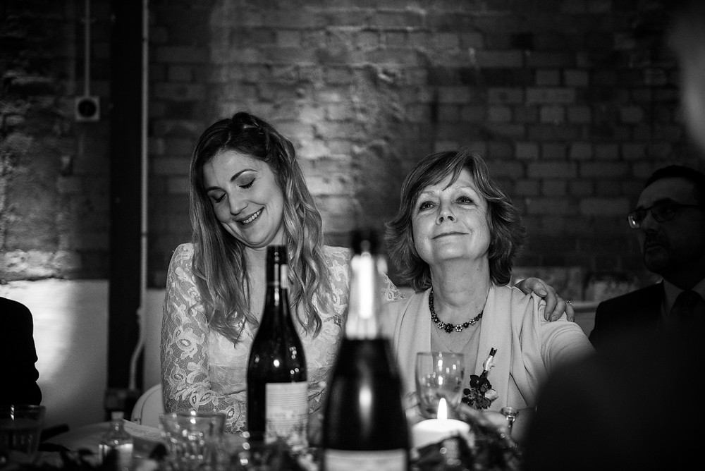 black & white reportage image of bride with her mother during speeches
