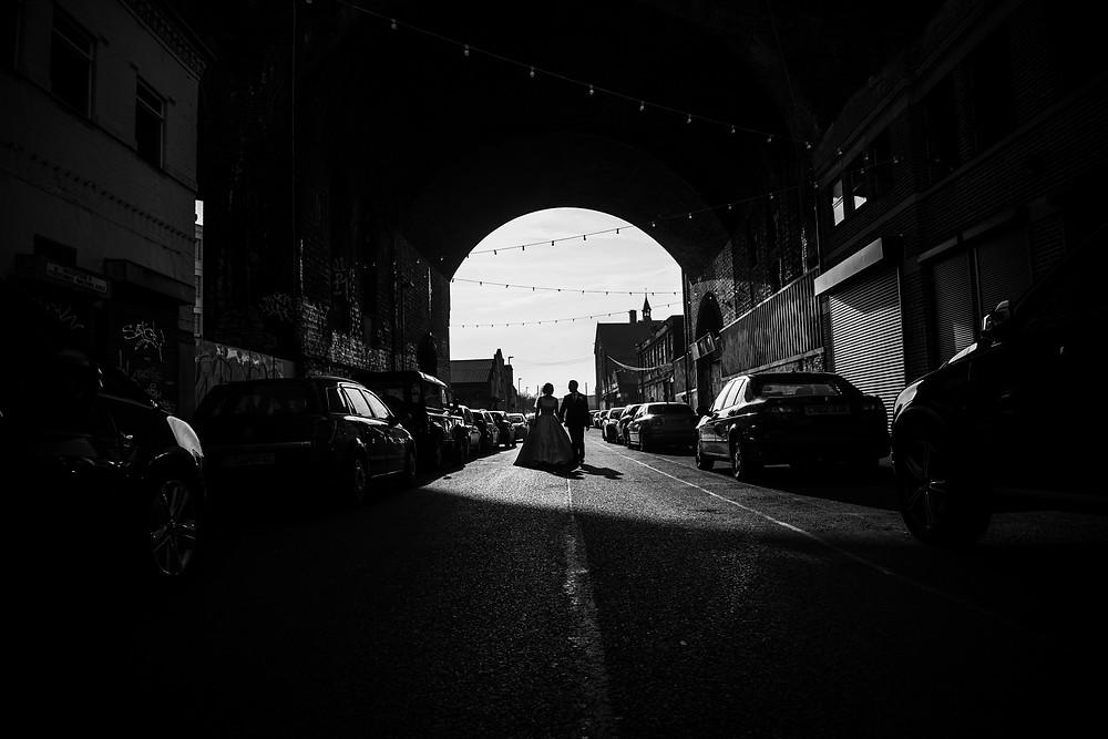 Bride & Groom walking underneath railway arch in Digbeth after their wedding