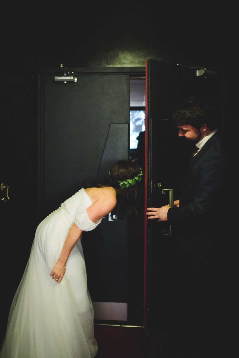 Bride peering around the door at the electric cinema before her wedding