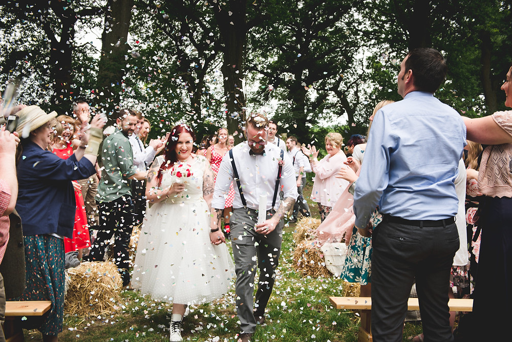 bride & groom having confetti thrown over them in the woods