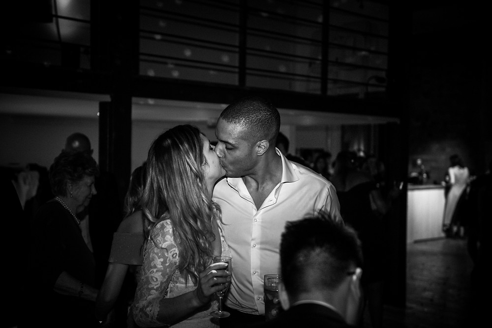 b&w documentarty wedding photograph of bride & groom kissing on the dancefloor