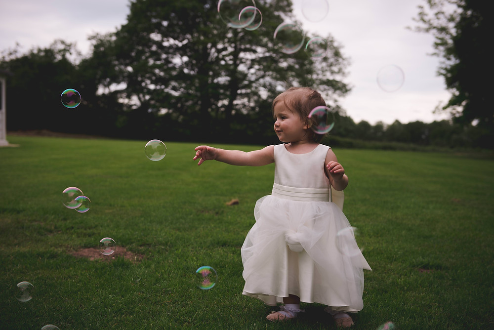 flower girl playing with bubbles at Staffordshire wedding reception