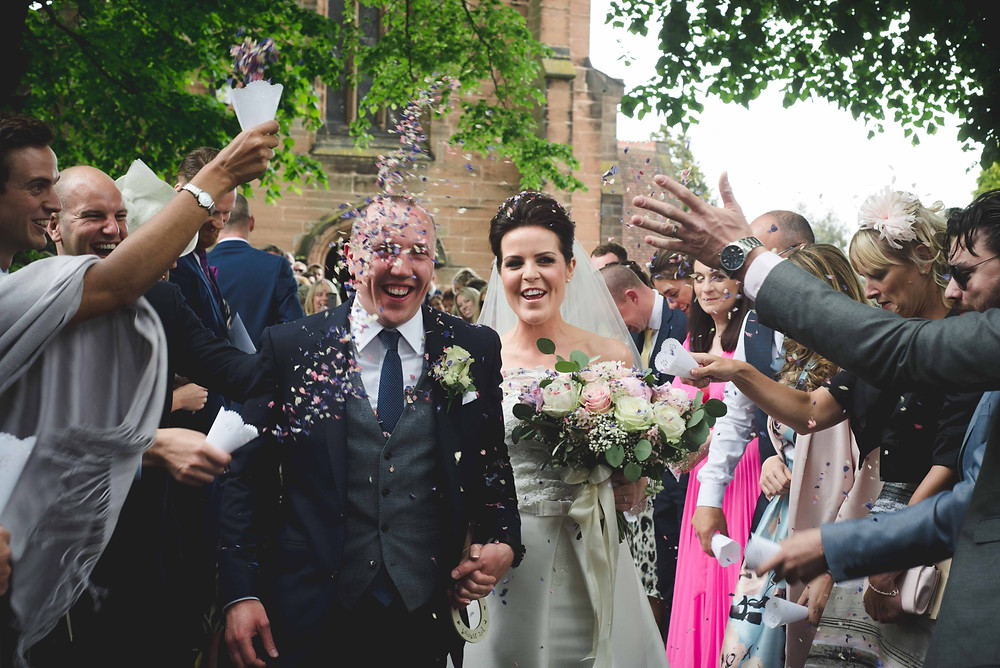Bride and Groom at Staffordshire wedding getting confetti thrown all over them them