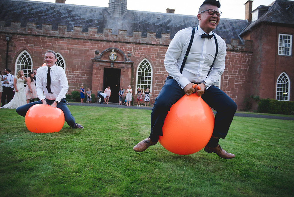 Wedding guests at Hartlebury Castle having space hopper races