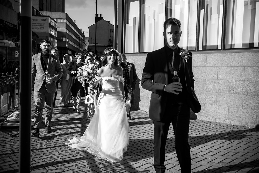 black & white storytelling photograph of bride & groom making their way through central birmingham to their wedding reception