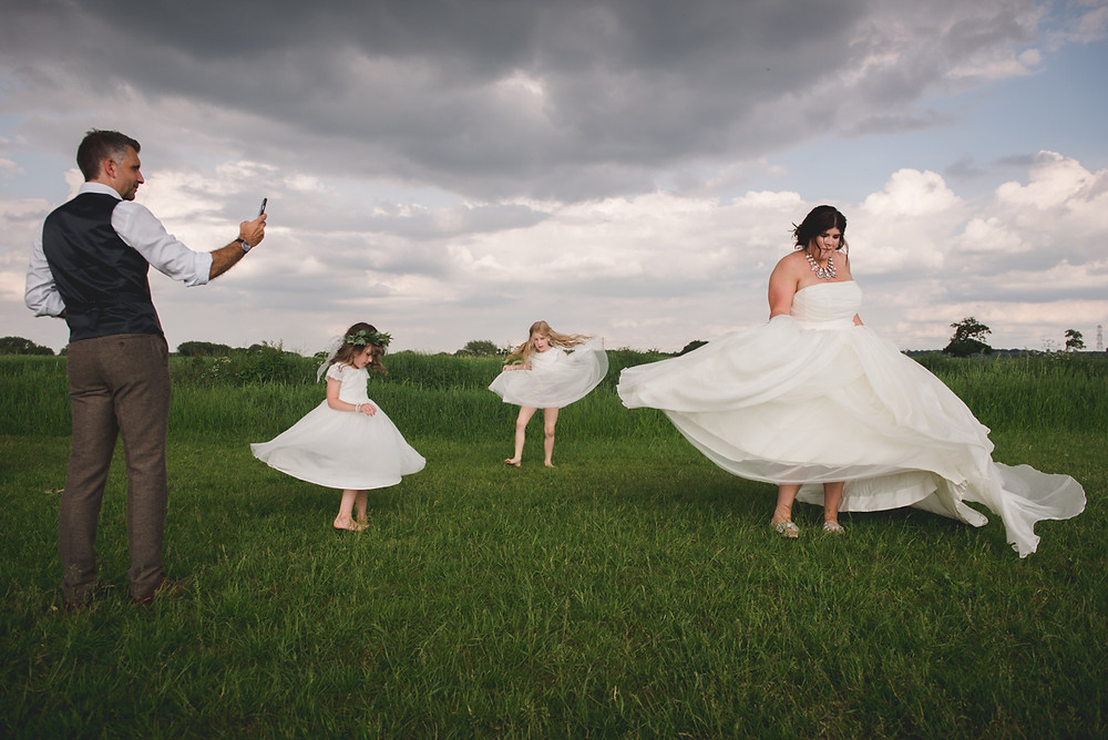 Bride and flower girls spinning around on the spot in a derbyshire field at tipi wedding