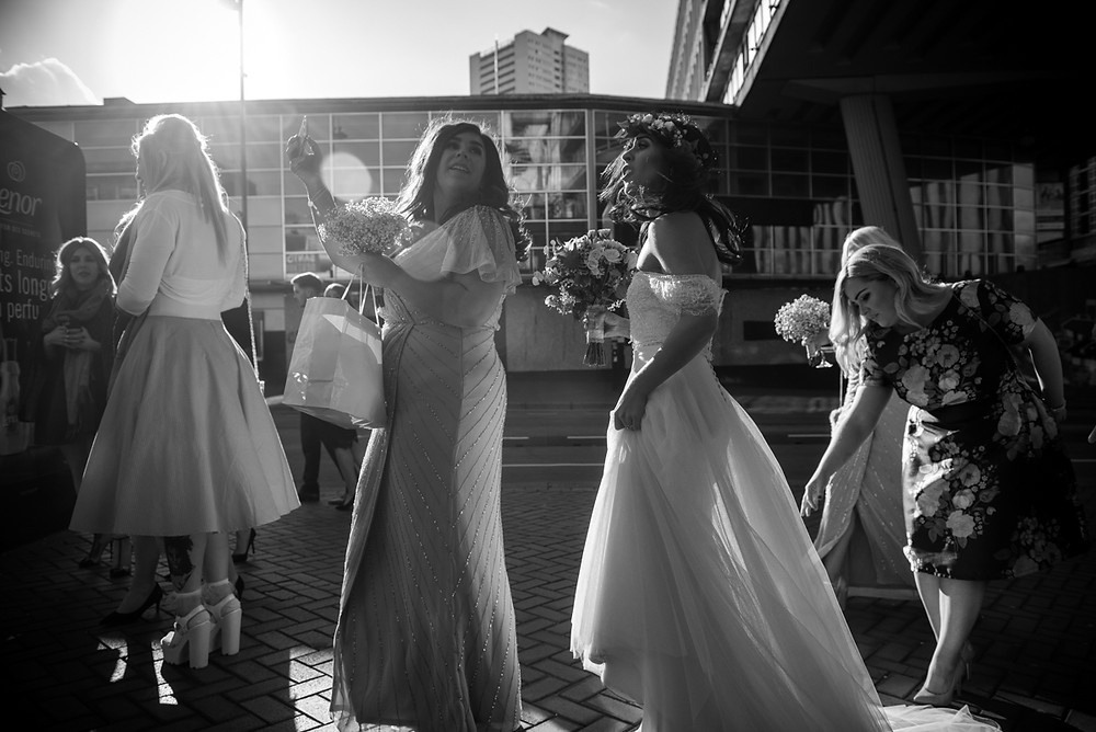 black & white backlit photograph of bride getting her dressed straightened as she pauses to talk to her bridesmaid in central birmingham