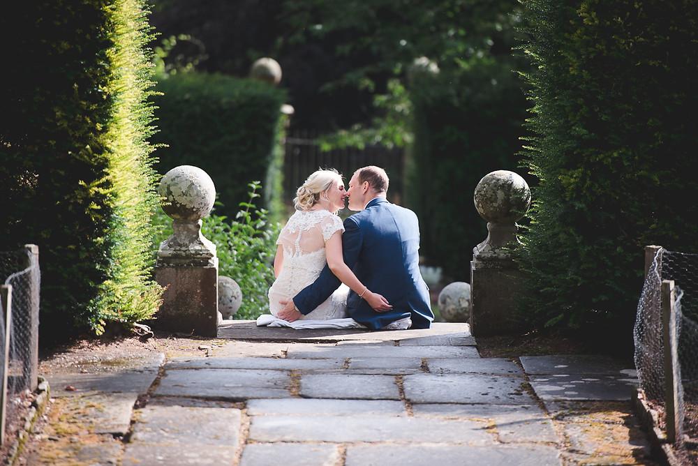 Bride & Groom sitting on steps in How Caple Court gardens