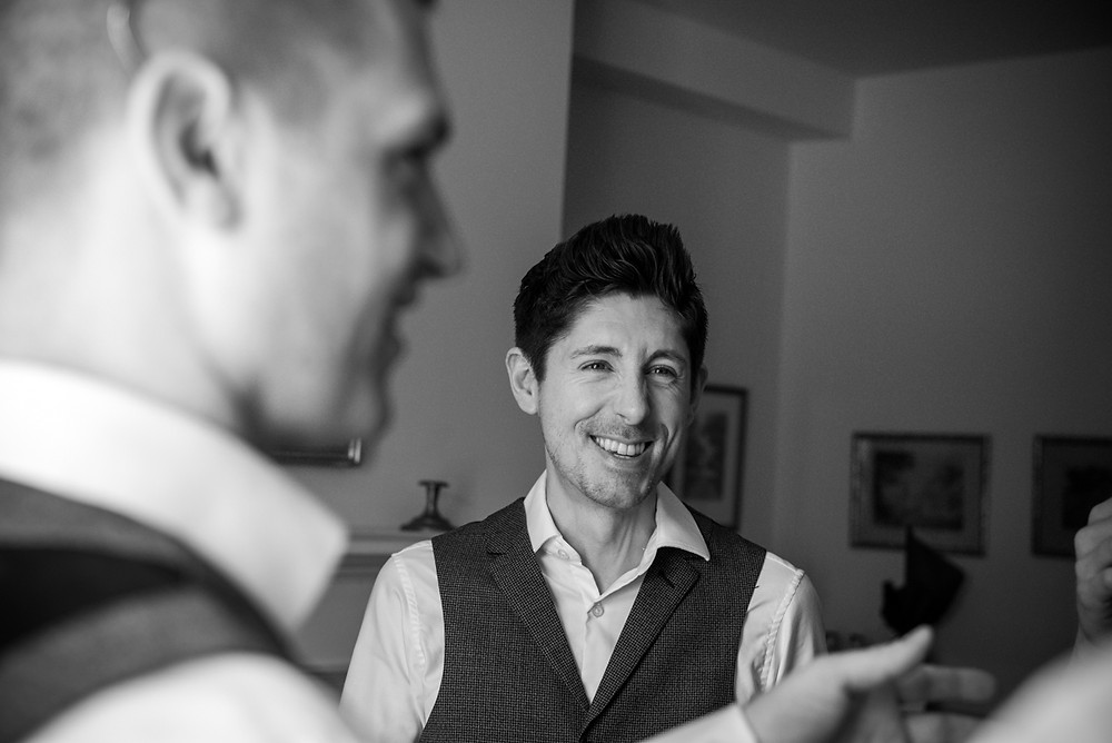 Smiling groom in candid photograph during morning prep at Wethele Manor wedding
