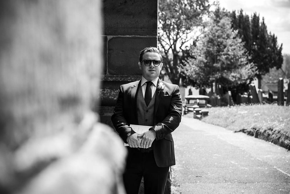 Usher waiting outside Brewood church before a wedding