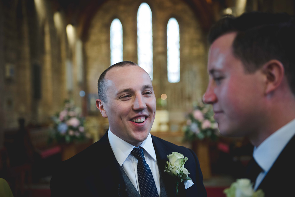 smiling groom waiting inside St Mark's church in Staffordshire