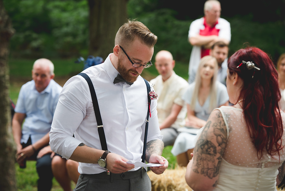 groom reading his vows during open air wedding