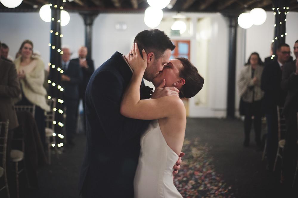 Post wedding ceremony kiss between Bride & Groom after their Bond Company wedding in Birmingham