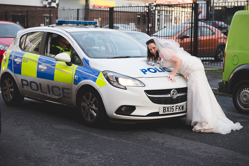 Laughing bride sprawled across the bonnet of a police car in Digbeth in Birmingham