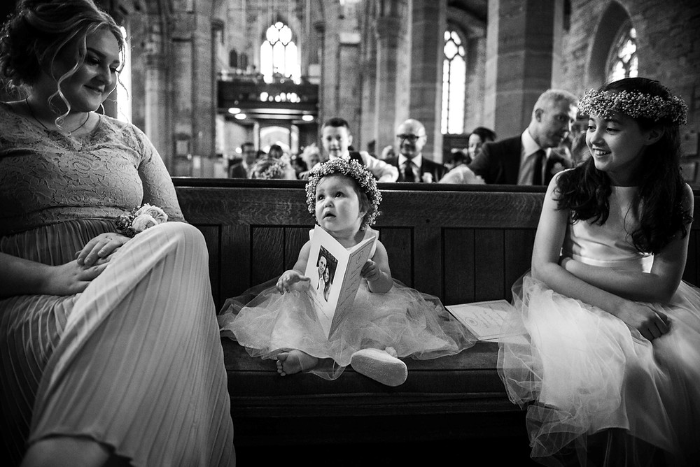 Cute flower girl holding order of service at Staffordshire church wedding